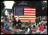 Political speech on town green with american flag in background